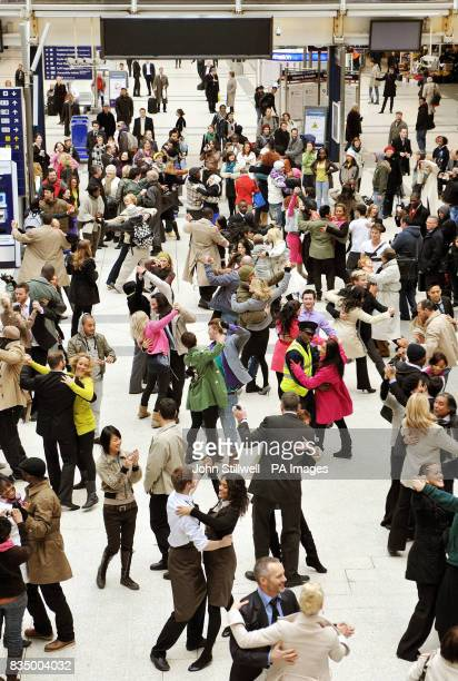 A huge crowd of dancers entertain commuters as they dance during the filming of a mobile phone commercial at Liverpool Street station in London