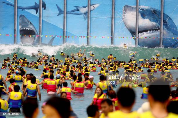 XI'AN CHINA JULY 05 Huge crowds of people play at THEBES Happiness Water World during a continuous high temperature on July 5 2014 in Shaanxi Xi'an...