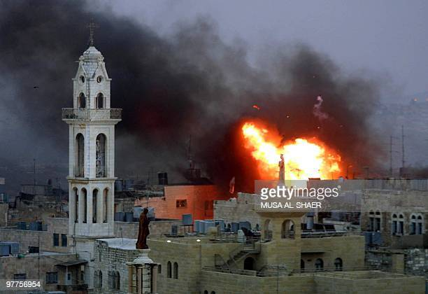 A huge fire rages following an explosion in the center of the West Bank town of Bethlehem 06 April 2002 near the Assyrian Church in the town's market...