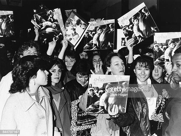 A huge group of young women fans of the Norweigan pop group 'AHa' happily wave their records in the air as they wait outside the HMV store to see the...