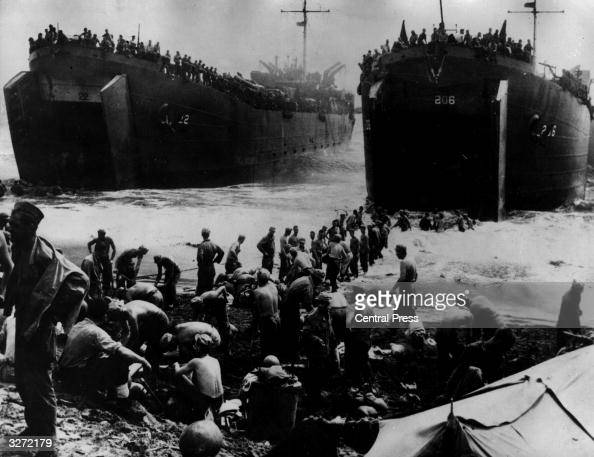 A huge landing craft from the American Navy arrives offshore at Leyte Island bringing troops and supplies Soldiers on the beach fill sandbags to make...