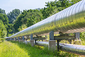 Huge metal gas pipeline distributing gas outside. In the Netherlands they extract gas as energy out of the ground. It is distributed above the ground through large and long gas pipelines like you see