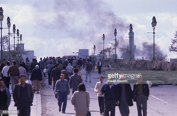 A huge mural of Saddam Hussein is seen at a distance where people cross a bridge with rubber tyre smoke rising over it in central Baghdad during the...