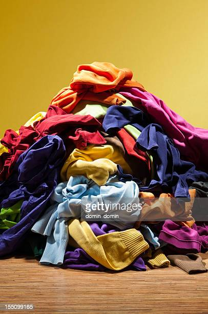 Huge pile heap of dirty clothes on golden background