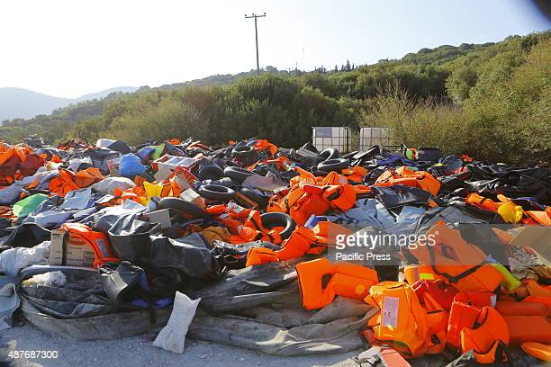 A huge pile of life jackets other inflatable devices and inflatable rubber dinghies that were used by the refugees coming ashore Hundreds of refugees...