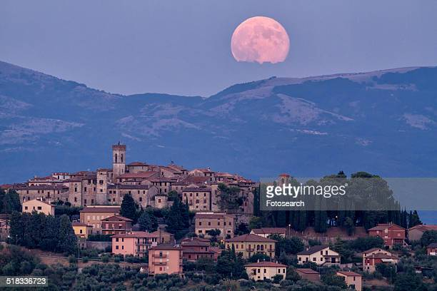 Huge pink full moon over hills above hilltop town of MonteCastello di Vibio, Umbria, Italy