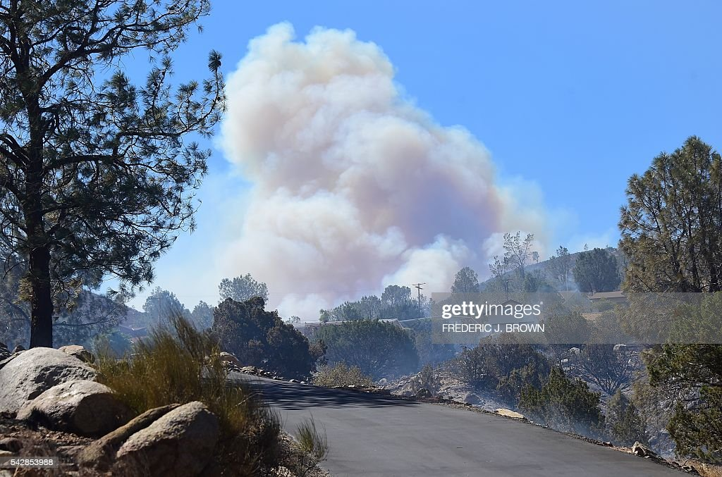 A huge plume of smoke rises from behind the mountains in Lake Isabella, California on June 24, 2016. An intense wildfire broke out yesterday afternoon scorched dozens of homes and structures in this mountainous community northeast of Bakersfield in Kern County. / AFP / FREDERIC