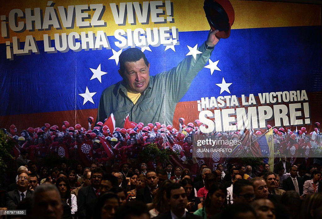 A huge poster of late Venezuelan President Hugo Chavez decorates the room as the country's Minister of Petroleum and Mining and president of the state owned oil company PDVSA, Rafael Ramirez, gives the 2012 annual report of the company, at its headquarters in Caracas, on May 3, 2013. AFP PHOTO