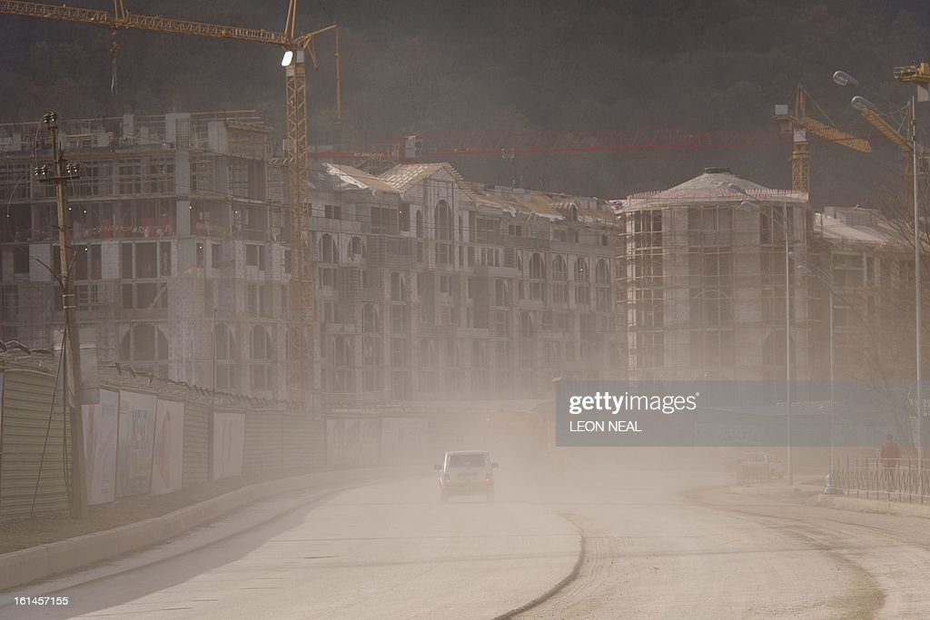 Huge quantities of dust is thrown into the air on a busy stretch of road amid signs of the ongoing construction work in Krasnaya Polyana, near Sochi on February 11, 2013. With a year to go until the Sochi 2014 Winter Games, tests events and World Championship competitions are underway.