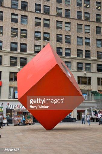 Huge red cube balanced on corner.