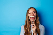 Huge smile through magnifying glass of young woman