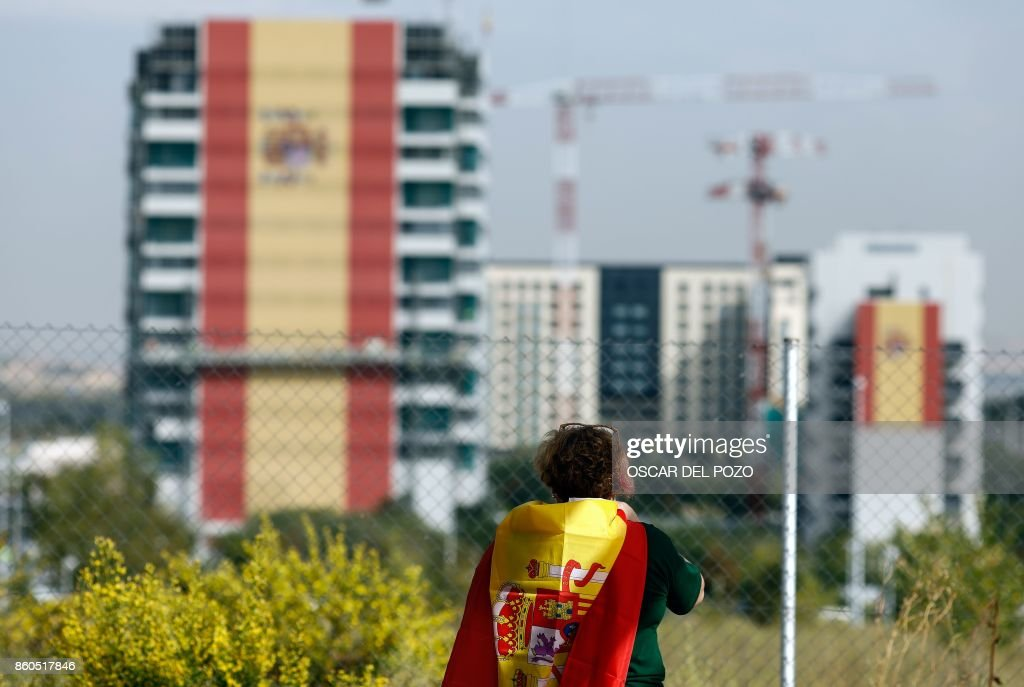 TOPSHOT - A huge Spanish flag covers the facade of a building under construction in Valdebebas neighborhood in Madrid, October 12, 2017. Spain marks its national day under high tension as the country reels from the biggest challenge to unity in a generation with its Catalan region threatening to break away. /