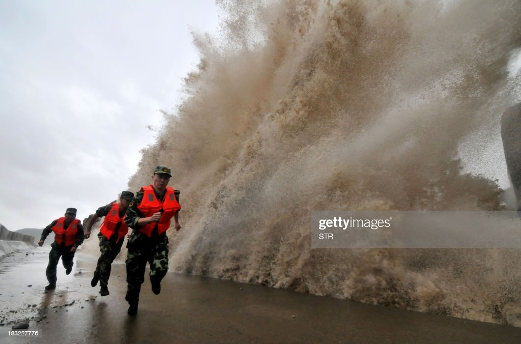A huge wave hits the dike as guards run along it as Typhoon Fitow moves to make its landfall in Wenling, east China's Zhejiang province on October 6, 2013. China was on its highest alert for Typhoon Fitow on October 6, with tens of thousands evacuated as the storm was set to slam into the east coast. CHINA