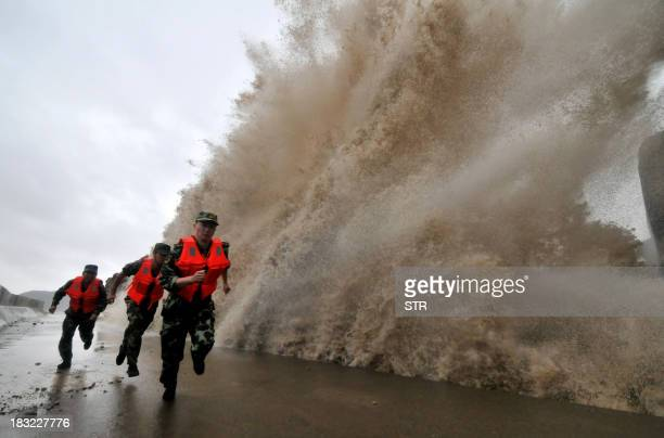 A huge wave hits the dike as guards run along it as Typhoon Fitow moves to make its landfall in Wenling east China's Zhejiang province on October 6...