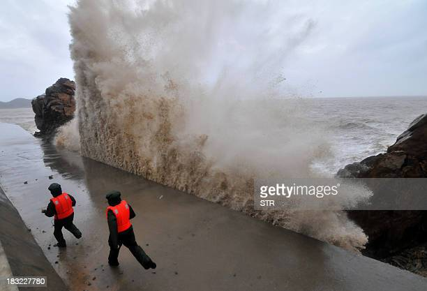 A huge wave hits the dike as guards run along it Typhoon Fitow moves to make its landfall in Wenling east China's Zhejiang province on October 6 2013...