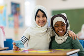 Two Muslim girls are sitting in their classroom. They are embracing and smiling at the camera.