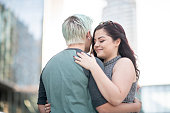 A lesbian couple are hugging outdoors. It's a sunny day in the downtown of a big city.