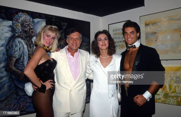 Hugh and Christie Hefner pose for a photograph with a female and male bunny October 29 1985 at the reopening of the Playboy Club in New York City