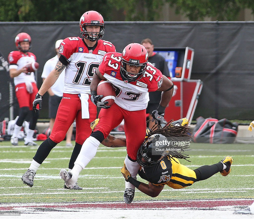 Hugh Charles of the Calgary Stampeders breaks free from a tackle by Rico Murray of the Hamilton TigerCats in a CFL game at Ron Joyce Stadium on...