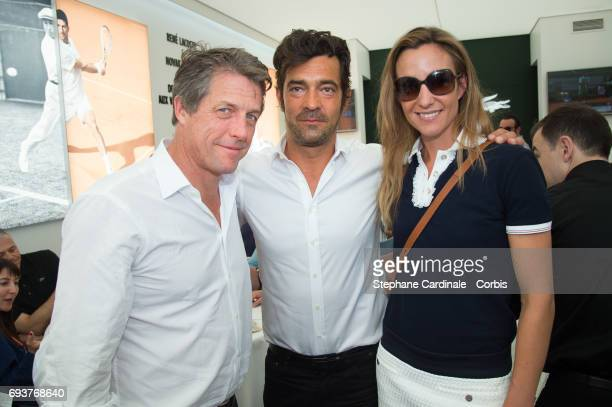 Hugh Grant and his companion Anna Eberstein and Lacoste CEO Thierry Guibert attend the French Tennis Open 2017 Day Twelve at Roland Garros on June 8...