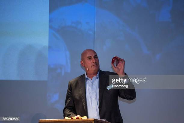 Hugh Grant chairman and chief executive officer for Monsanto Co holds up an apple during the Global Agribusiness Forum in Sao Paulo Brazil on...