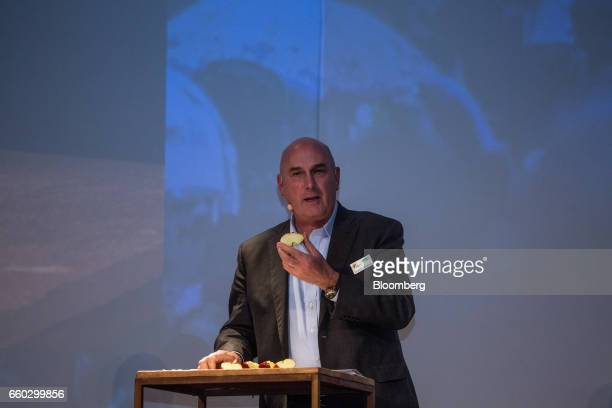 Hugh Grant chairman and chief executive officer for Monsanto Co speaks while holding up an apple during the Global Agribusiness Forum in Sao Paulo...