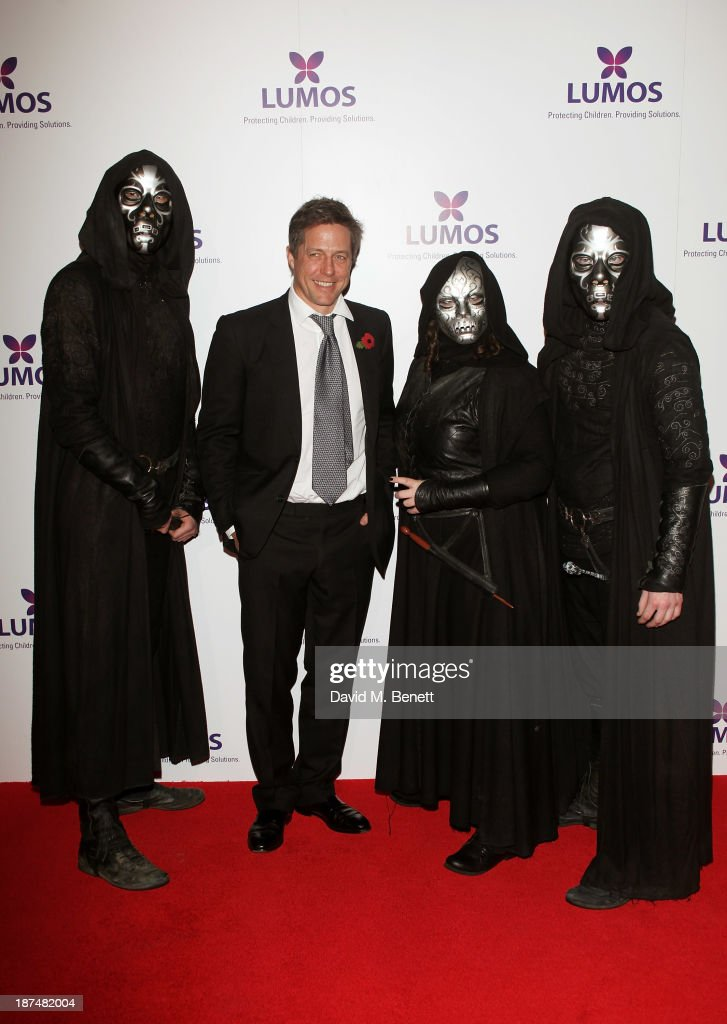 Hugh Grant (2L) poses with Death Eaters at the Lumos fundraising event hosted by J.K. Rowling at The Warner Bros. Harry Potter Tour on November 9, 2013 in London, England.