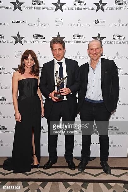 Hugh Grant winner of the Best Actor award for 'Florence Foster Jenkins' poses with presenters Ophelia Lovibond and William Sieghart at The London...