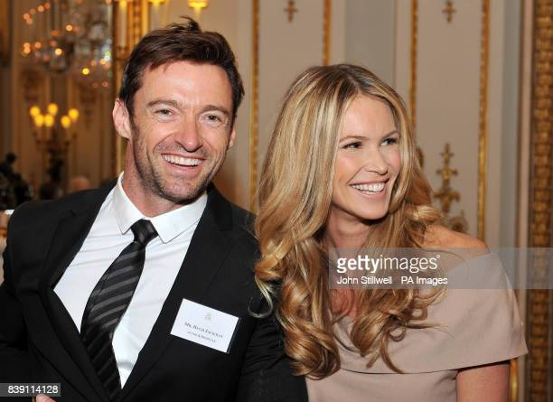 Hugh Jackman and Elle Macpherson wait to meet Queen Elizabeth II in the white drawing room at Buckingham Palace before a Royal reception for members...