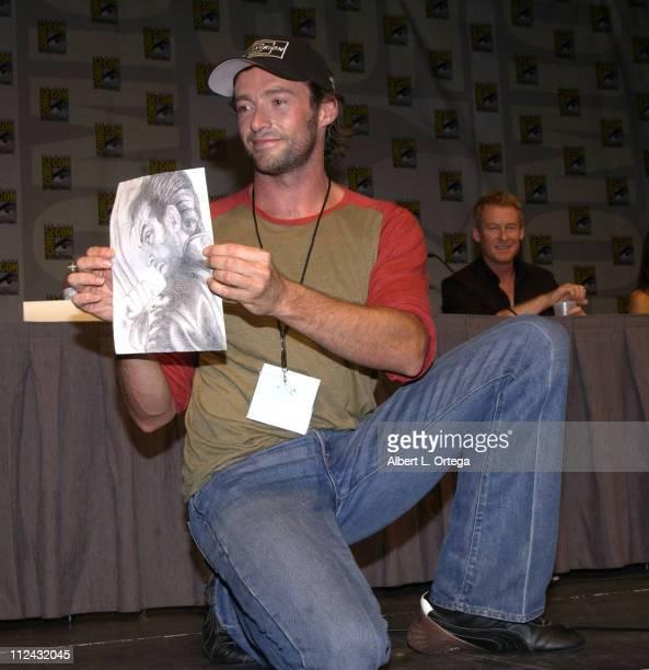 Hugh Jackman holding up a fan's sketch of Wolverine