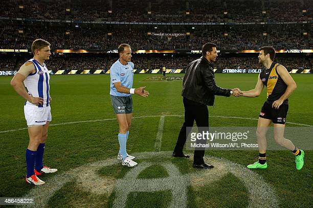 Hugh Jackman shakes hands with Trent Cotchin of the Tigers as Jack Ziebell of the Kangaroos looks on during the 2015 AFL round 23 match between the...