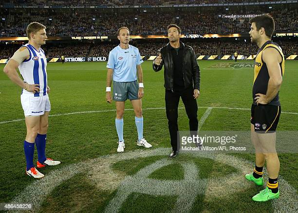 Hugh Jackman tosses the coin with Jack Ziebell of the Kangaroos and Trent Cotchin of the Tigers during the 2015 AFL round 23 match between the...