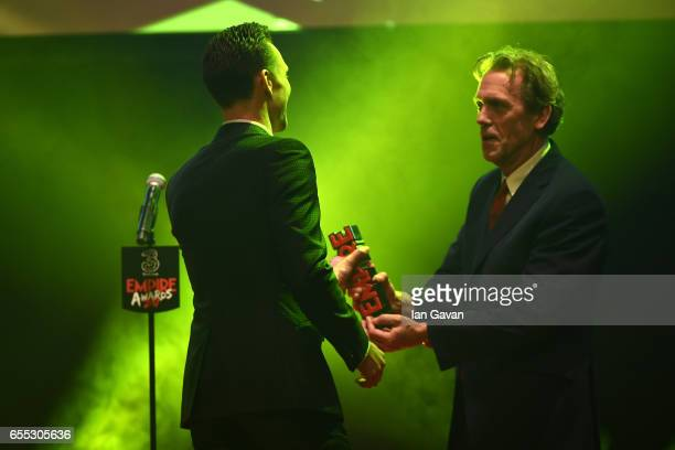 Hugh Laurie presents the Empire Hero award to Tom Hiddleston during the THREE Empire awards at The Roundhouse on March 19 2017 in London England