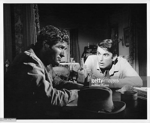 Hugh O'Brian and Bob Evans having conversation over drinks in a scene from the film 'The Fiend Who Walked The West' 1958