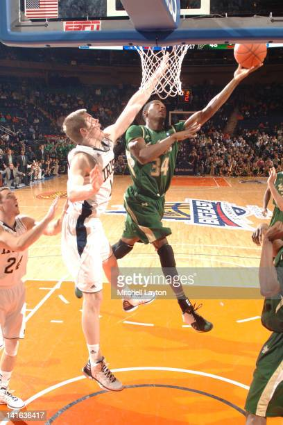 Hugh Robertson of the South Florida Bulls drives to the basket by Scott Martin of the Notre Dame Fighting Irish during a quarterfinal game at the...