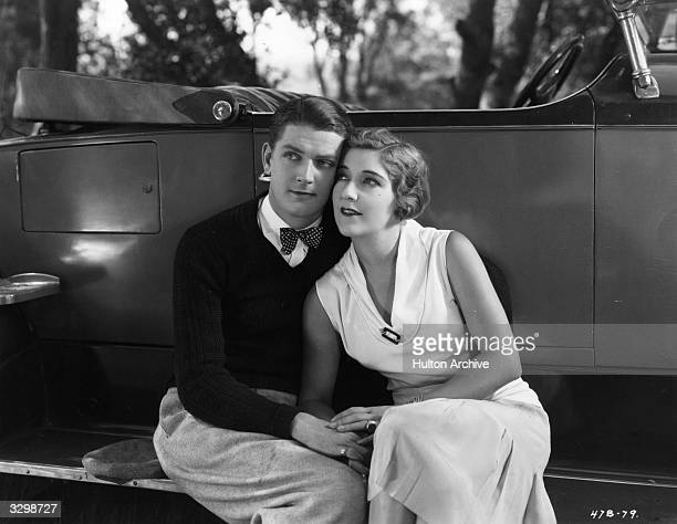 Hugh Trevor and Aileen Pringle canoodling on the running board of a vintage sports car in a scene from the RKO film 'Night Parade' aka 'Sporting Life'