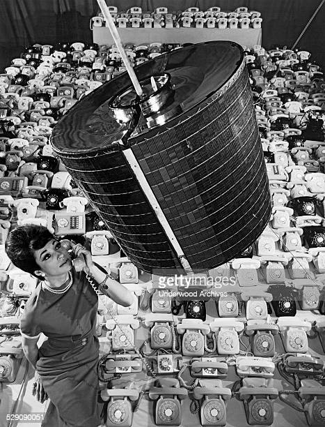 A Hughes Aircraft Company employee uses one of the 480 telephones that the Intelsat 1 'Early Bird' communications satellite can transmit in two way...