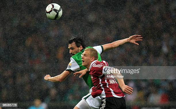 Hugo Almeida of Bremen and Andreas Wolf of Nuernberg jump for a header during the Bundesliga match between Werder Bremen and 1 FC Nuernberg at the...