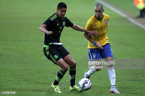 Hugo Ayala of Mexico fights for the ball with Diego Tardelli of Brazil during a friendly match between Brazil and Mexico at Allianz Parque Stadium on...