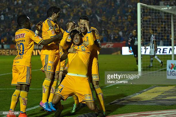 Hugo Ayala of Tigres celebrates with teammates after scoring the tying goal during a quarterfinal second leg match between Tigres UANL and Pachuca as...