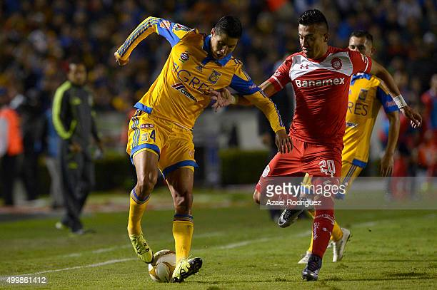 Hugo Ayala of Tigres fights for the ball with Fernando Uribe of Toluca during the semifinals first leg match between Tigres UANL and Toluca as part...