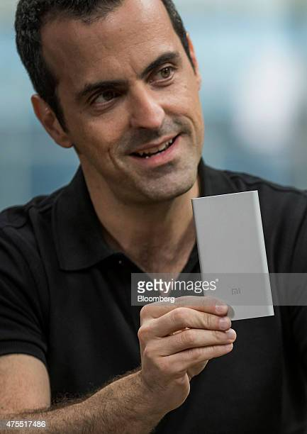 Hugo Barra vice president of global operations at Xiaomi Corp holds a Xiaomi Corp Mi Power Bank while speaking during a Bloomberg Studio 10 interview...