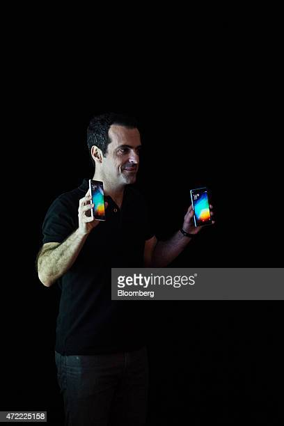 Hugo Barra vice president of global operations at Xiaomi Corp holds Mi 4i smartphones during a news conference in Hong Kong China on Tuesday May 5...