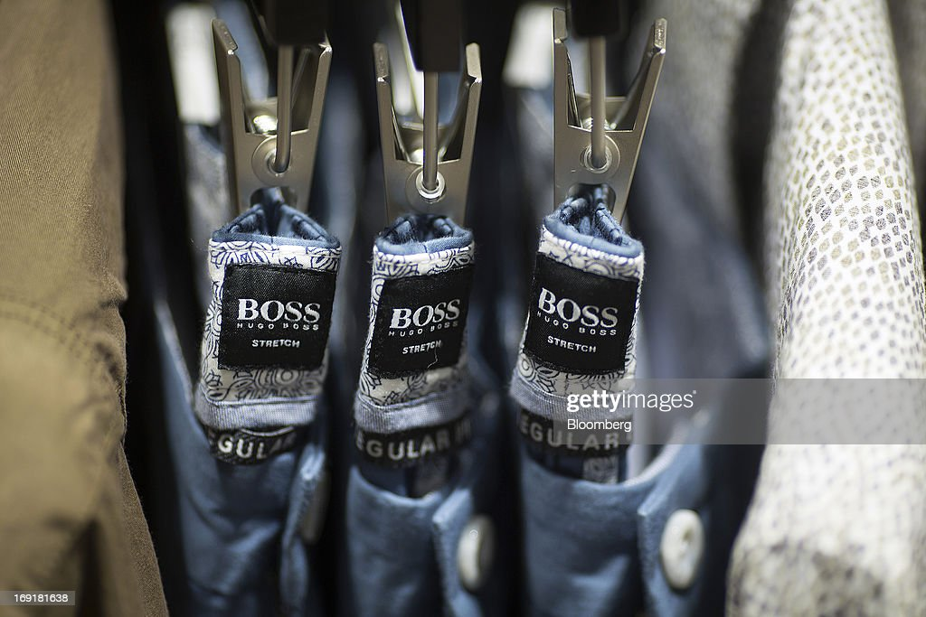 Hugo Boss logos sit inside the waistbands of mens trousers inside Hugo Boss AG's store on Regent Street in London, U.K. on Tuesday, May 21, 2013. Hugo Boss AG reiterated its earnings forecast for the year after the German luxury-clothing maker said its retail business increased sales by 14 percent in the first quarter as it opened more outlets. Photographer: Simon Dawson/Bloomberg via Getty Images