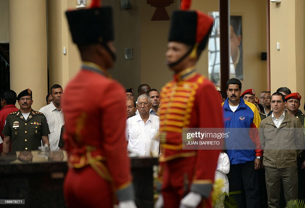 Hugo Chavez's father Hugo de los Reyes Chavez (C), Venezuelan President Nicolas Maduro (2nd R)and Vice-President Jorge Arreaza (R) attend a ceremony three months after Hugo Chavez's death, at the Cuartel de la Montana in Caracas, on June 05, 2013. AFP PHOTO