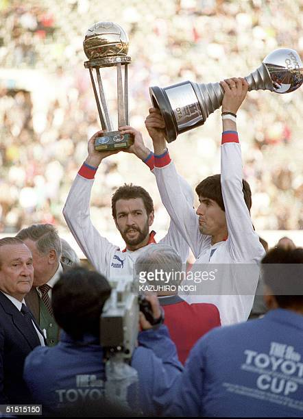 Hugo Eduardo de Leon and Santiago Javier Ostolaza of Nacional de Montevideo hold the trophies high after winning the Toyota Cup World Club Soccer...