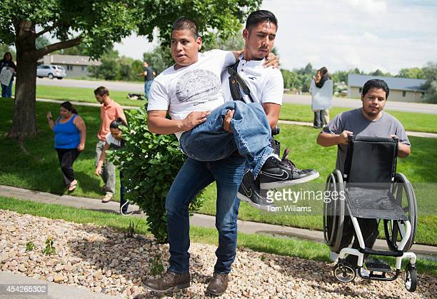 Hugo Juarez carries Veni Noya who suffers from spina bifida after an action with Dreamers outside the Greeley office of Rep Cory Gardner RColo to...