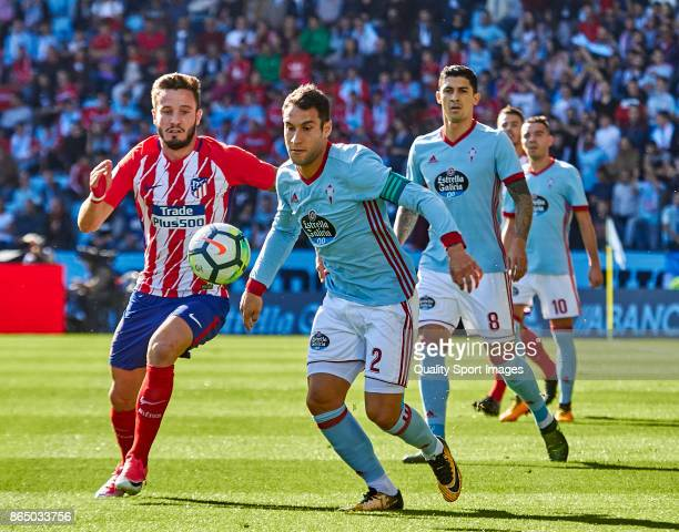 Hugo Mallo of Celta de Vigo is challenged by Saul Ñiguez of Atletico de Madrid during the La Liga match between Celta de Vigo and Atletico Madrid at...