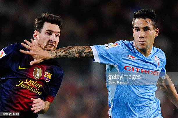Hugo Mallo of RC Celta de Vigo grabs Lionel Messi of FC Barcelona during the La Liga match between FC Barcelona and RC Celta de Vigo at Camp Nou on...