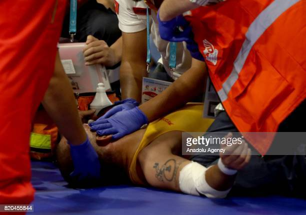 Hugo Miguel Passos of Portugal receives medical treatment by paramedics during his men's 59 kg grecoroman wrestling fight against Muhammet Akdeniz of...